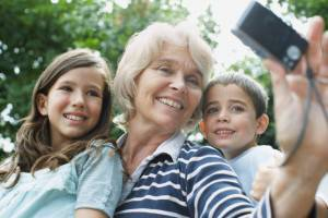 Grandmother taking self-portrait with grandchildren