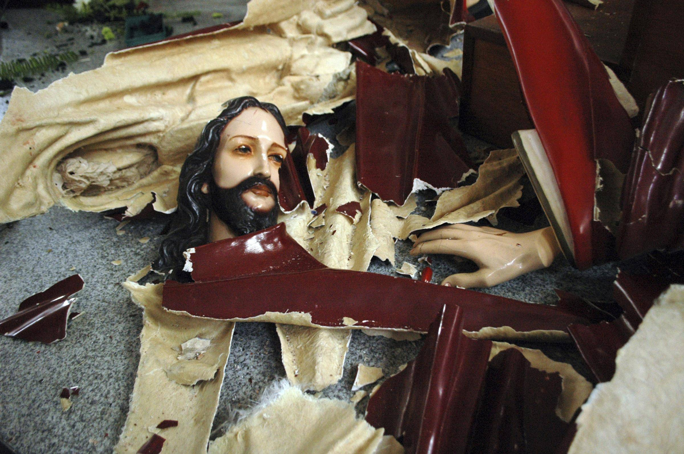 A statue of Jesus Christ is left smashed on the floor at the church that was attacked by Muslim hardliners in Temanggung, Central Java, Indonesia, Tuesday, Feb. 8, 2011. Hundreds of Islamic hard-liners stormed a courthouse and set two churches on fire Tuesday in central Indonesia to protest what they considered a lenient sentence for a Christian convicted of blaspheming Islam. (AP Photo/Slamet Riyadi)