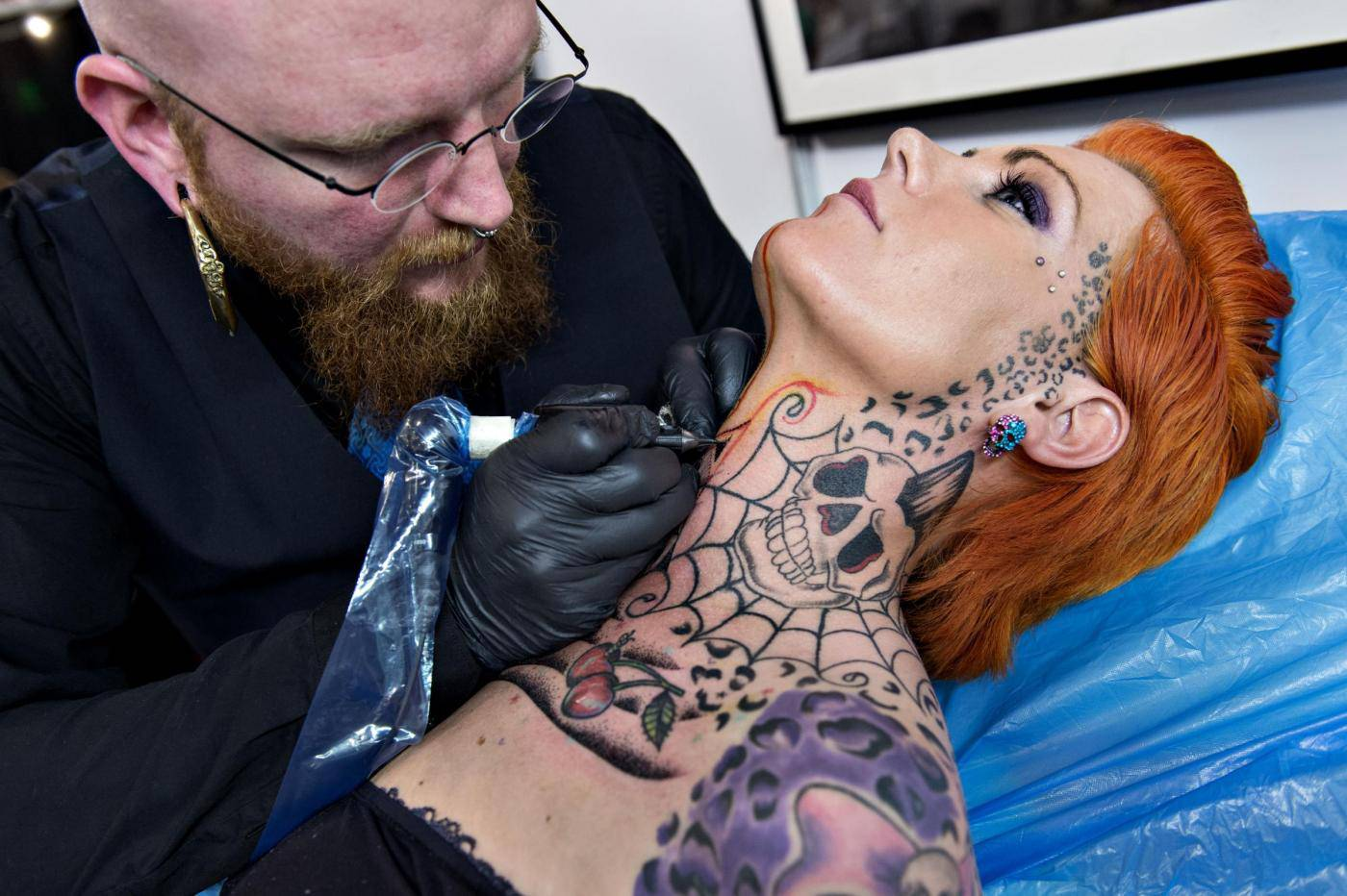 Pernille Ferdinandsen receives a neck tattoo from Peter Madsen during the third Copenhagen Ink Festival which opened Thursday May 9, 2013 in Copenhagen, Denmark, the biggest tattoo festival in Northern Europe. During the three days, 180 of the world's best and most celebrated national and international tattoo artists show the audience their skills in making art on the body and tattoo's on the audience. (AP Photo/Polfoto, Lars Krabbe) DENMARK OUT