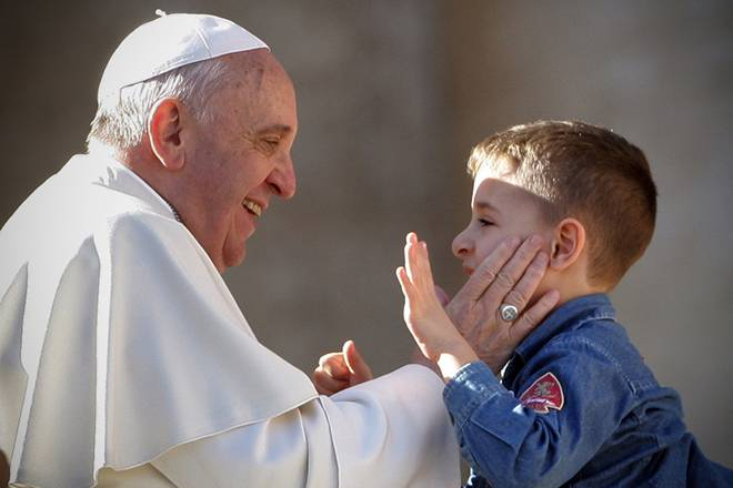 VATICAN CITY, VATICAN - FEBRUARY 14: Pope Francis greets a boy as he attends a meeting with engaged couples from all over the world gathered today, on the feast of St. Valentine, in St. Peter's Square February 14, 2014 in Vatican City, Vatican. During the event, organised by the Pontifical Council for the Family, Pope Francis emphasised that living together is 'an art, a patient, beautiful and fascinating journey' which can be summarized in three words: please, thank you and sorry. (Photo by Franco Origlia/Getty Images)