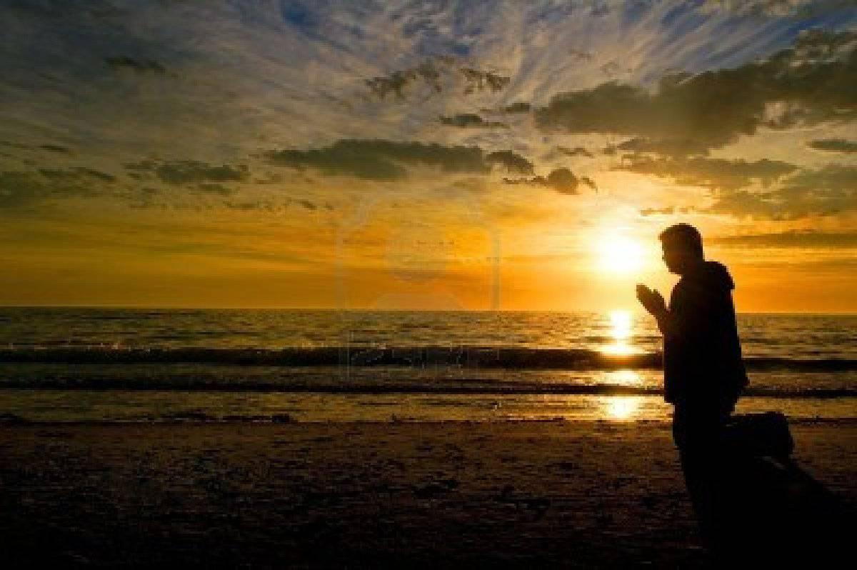 15367426-middle-aged-man-in-ginocchio-e-pregare-in-spiaggia-con-un-glorioso-tramonto-sullo-sfondo