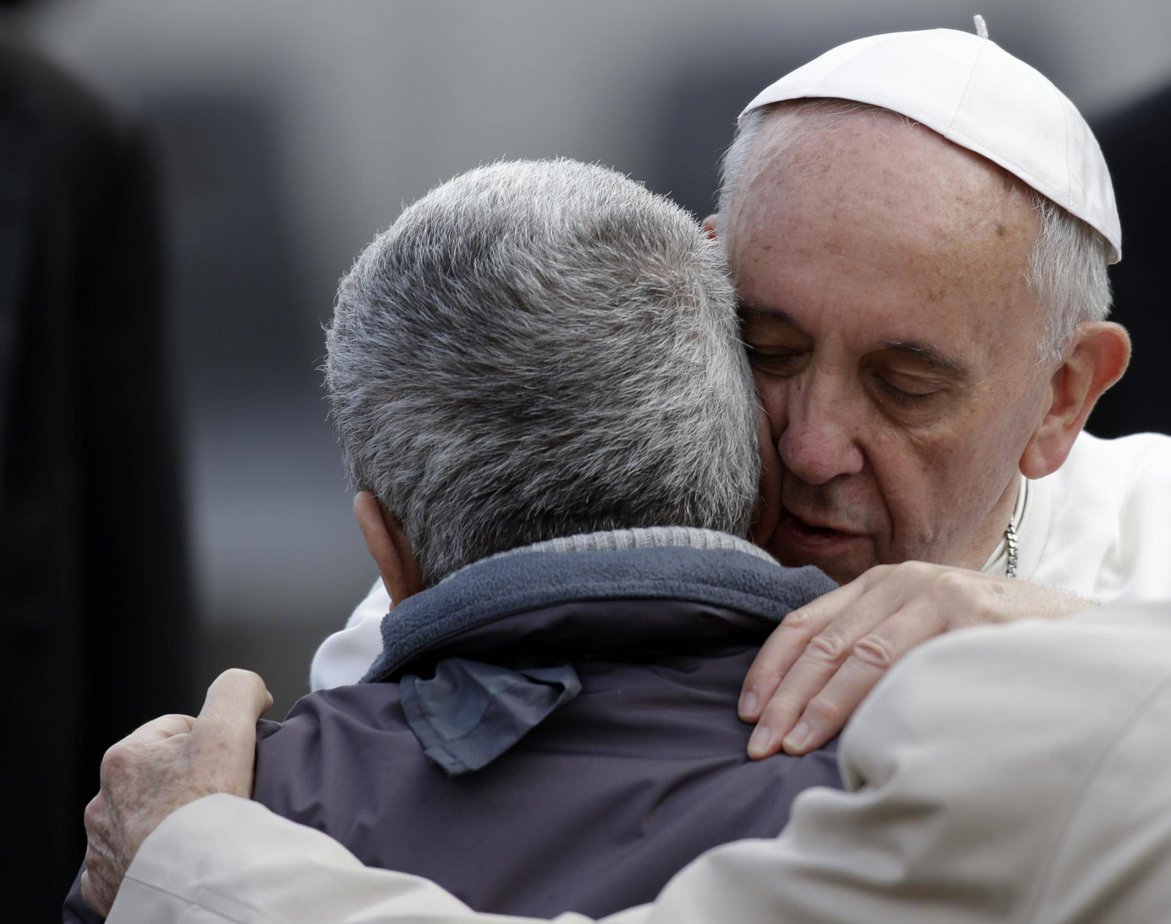 Pope Francis hugs a sick or disabled person at the end of his general audience in St. Peter's Square at the Vatican, Wednesday, Nov. 20, 2013. At the end of the general audience Pope Francis dedicates a few minutes greeting sick or disabled people. (AP Photo/Gregorio Borgia)