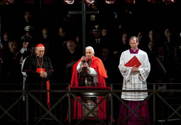 Pope Benedict XVI (C) holds the cross as he leads the Way of the Cross on Good Friday on April 2, 2010 at Rome's Colosseum.   AFP PHOTO / ANDREAS SOLARO (Photo credit should read ANDREAS SOLARO/AFP/Getty Images)