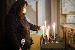 Fedele in chiesa che prega, accenda candela con mascherina per il Coronavirus