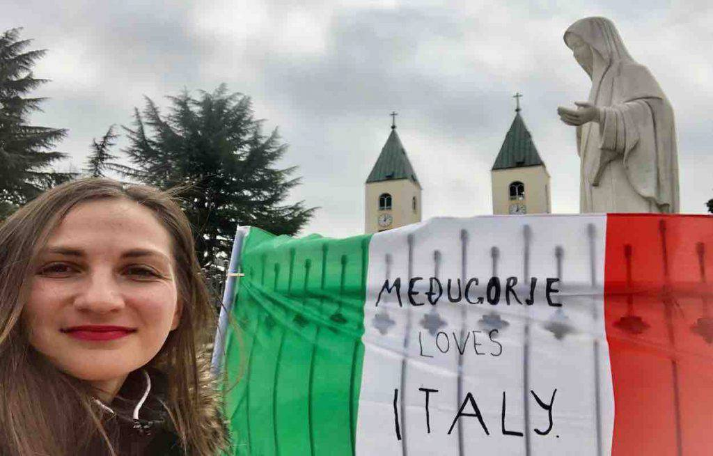 The Italian flag placed at the foot of the Madonna in Medjugorje
