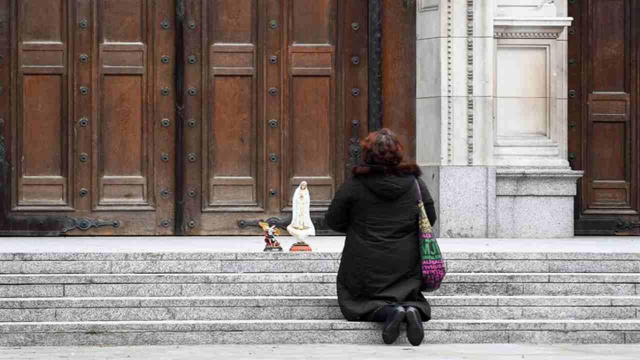 donna che prega davanti a una chiesa chiusa