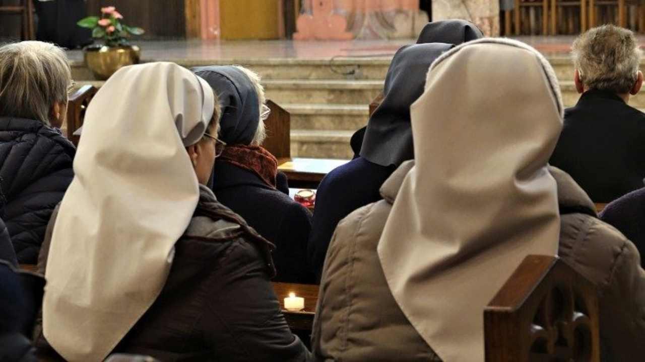 Suore che pregano in Chiesa