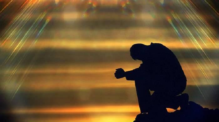 uomo in preghiera sotto la luce