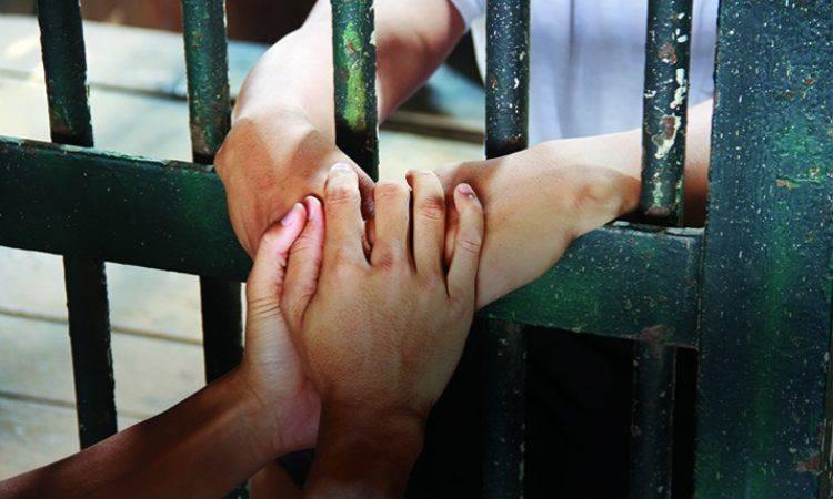 mani di detenuti che pregano insieme