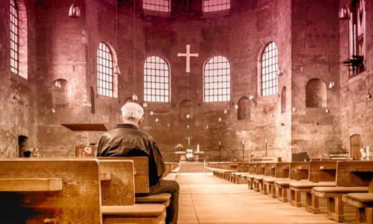 un uomo prega in chiesa
