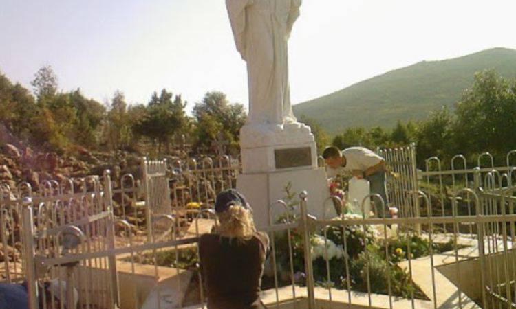 donna che prega ai piedi di maria