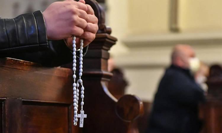 un uomo prega il rosario