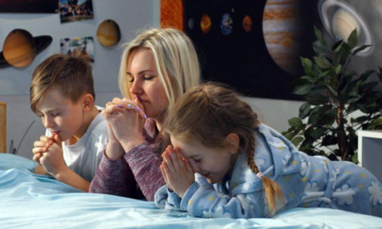 mamma che prega con i bambini