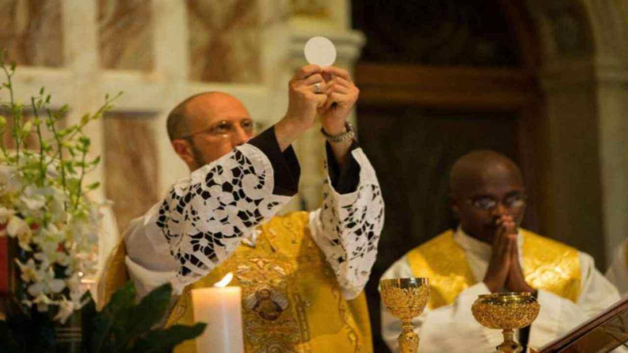 sacerdote che eleva l'eucarestia