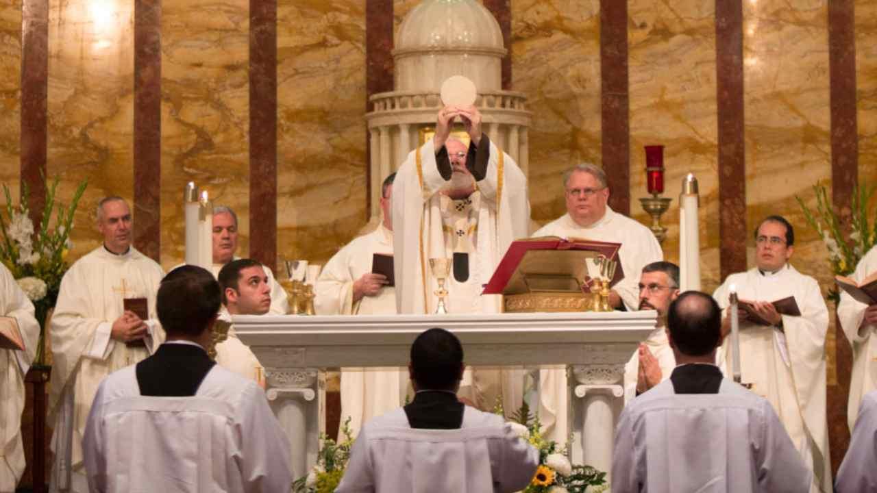 sacerdote innalza l'eucarestia