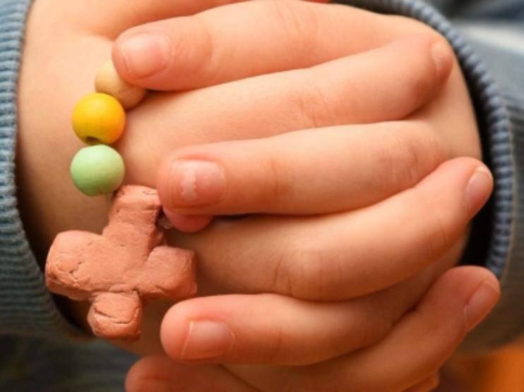 mani di un bambino che stringono il rosario